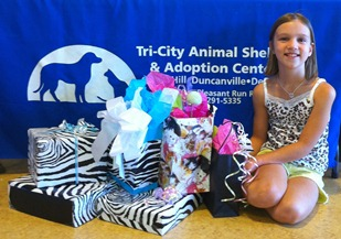 Picture of Abby with gifts she helped collect for animals at the shelter.