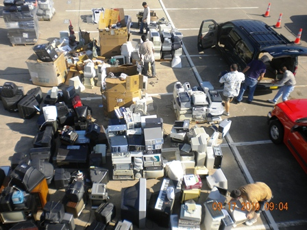 Picture taken from above the items brought to be recycled, bags and boxes full of electronics and pa