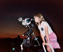 Little girl gazes through a telescope for a better view of the universe.