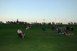 People on lawn chairs enjoying the music as the sun sets in the background..JPG