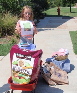 Picture of Hannah with the supplies she bought for the shelter.