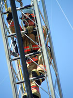 Fire fighter climbing the extended ladder of a Fire Engine